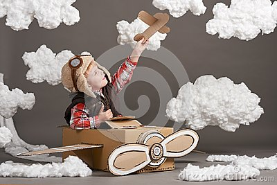 The boy plays in an airplane made of cardboard box and dreams of becoming a pilot, clouds of cotton wool on a gray background