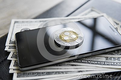 Crypto currency ripple xrp on smartphone and us dollars money background. Blockchain and cyber currency. Global money