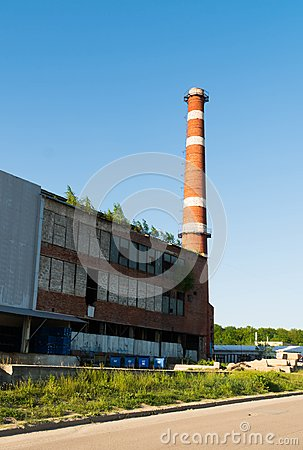 Isolated old aged weathered tall industrial factory chimney, red grungy brick smokestack grunge vintage