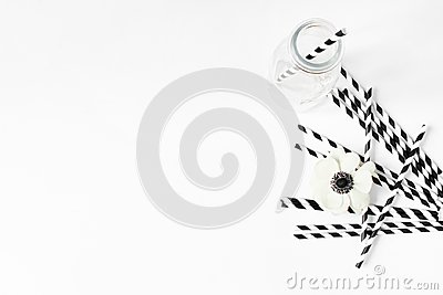 Breakfast or birthday party desktop scene. Composition with empty milk glass jar, black and white drinking paper straws