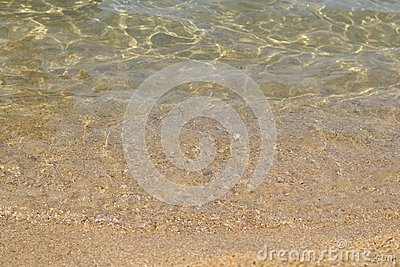 Sand beach, coastline and crystalline clear water in sea.