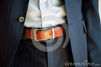 Man wears belt. Young businessman in casual suit with accessories. Fashion and clothing concept. Groom getting ready in