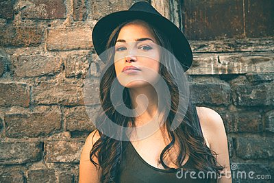 Young latino woman portrait with hat in front old house summer d