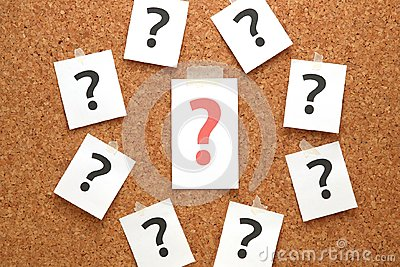 Red question mark on a piece of paper and many question marks on cork board.