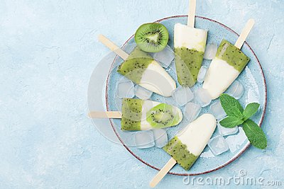 Plate of homemade fruity ice cream or popsicles from kiwi smoothie and yogurt top view. Summer refreshing sweets.