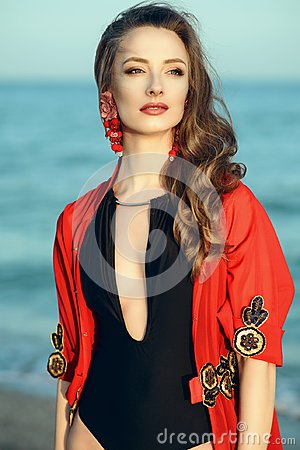 Beautiful woman standing at the seaside wearing trendy one piece halter neck swimsuit and red oriental beach cover up