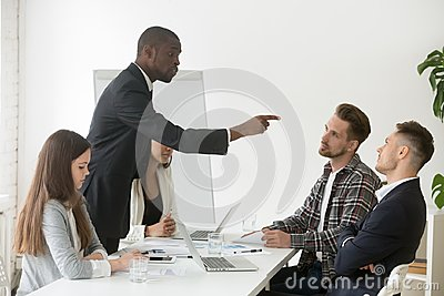 Angry rude african businessman pointing finger threatens colleag