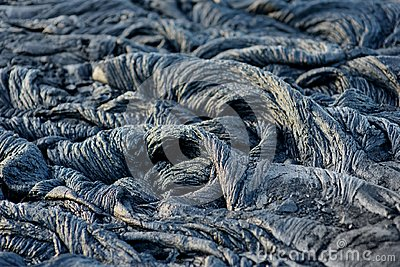 Smooth, undulating surface of frozen pahoehoe lava. Frozen lava wrinkled in tapestry-like folds and rolls resembling twisted rope