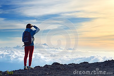 Tourist admiring breathtaking sunset views from the Mauna Kea, a dormant volcano on the island of Hawaii.