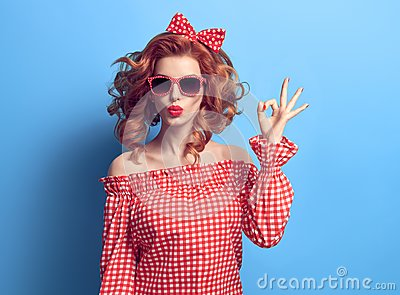 PinUp Beauty Girl Blowing lips, showing OK sign