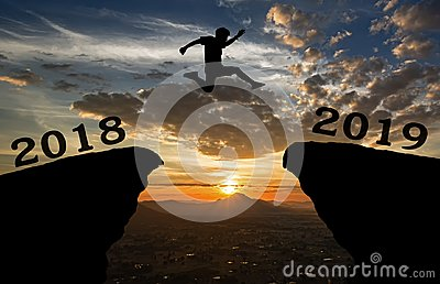 A young man jump between 2018 and 2019 years over the sun and through on the gap of hill silhouette