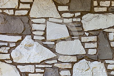 Wall background with irregular sized white and brown stones