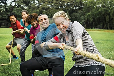 Diverse team competing in tug of war