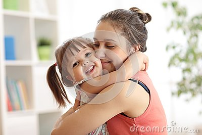 Love and family people concept - happy mother and child daughter hugging at home