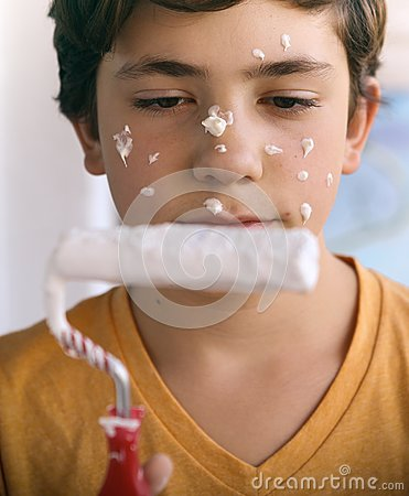 Smiling teenager boy with white paint roller and dirty face make repaint