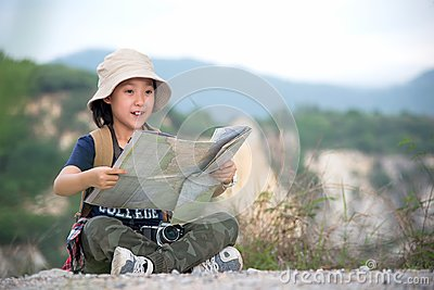 Children asian girl holding maps and travel backpacks standing in the mountain.