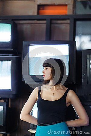 stock image of photo of young brunette on wall background with tv