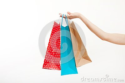 Female hand is holding shopping colorful bags on white background. Copy space and mock up. Template and blank background