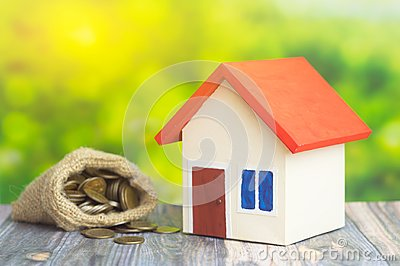 A home with red roof on green background with bag from sack with coins money inside concept of sell or buy home