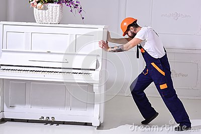 Heavy loads concept. Loader moves piano instrument. Courier delivers furniture, move out, relocation. Man with beard