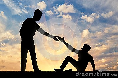 Silhouette of a man giving a helping hand to another man who fell to the ground