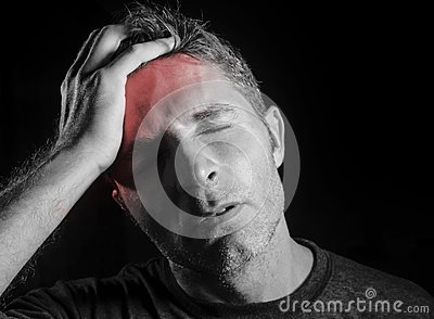 Young attractive and sad man suffering headache with hand on his tempo head in stress looking desperate and sick isolated black a