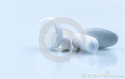 stock image of pile of white round and oblong shape tablet pills on white background. pharmaceutical industry. pharmacy or drugstore