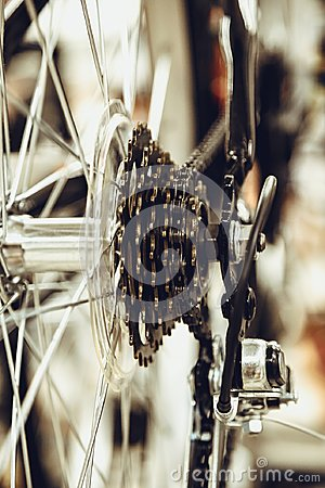 Bike speed changing assembly. Rear wheel. Steel bicycle chain. Transmission gears close-up.