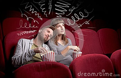 Cute couple in cinema watching movie