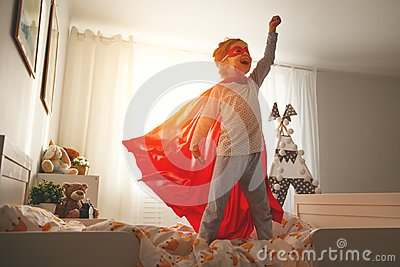 Child girl in a super hero costume with mask and red cloak