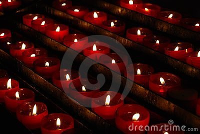 Row of small red church prayer candles