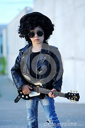 stock image of a boy like a rock star playing music on electric guitar.