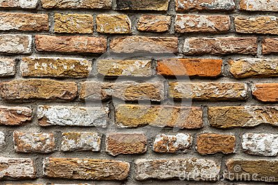 Close-up old vintage brick wall white yellow red tinted stones