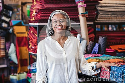 Smiling mature woman standing by cloth in her fabric store