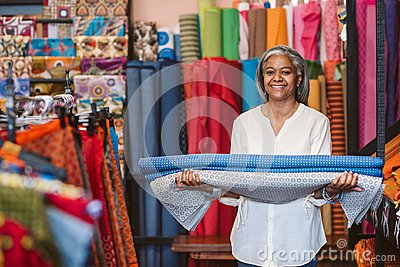 Smiling mature woman holding cloth rolls in her fabric shop