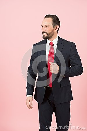 Bearded manager holds hand on flap of blue suit jacket wearing red tie on white shirt isolated over pink background