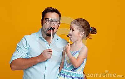 Happy father`s day! funny dad and daughter with mustache fooling