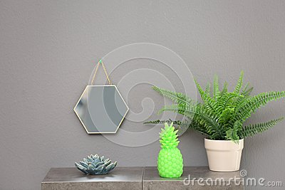 Stylish pineapple candle and houseplant on table