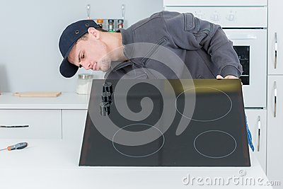 Young repairman installing appliances at clients home