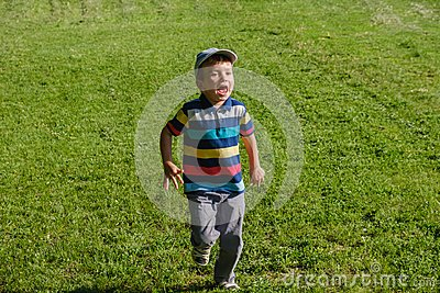 Young boy runs in a green field. Cute child running across park outdoors grass.