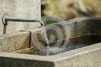 Water flows from a tap at the stone fountain