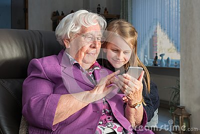 Grandmother showing her grandchild something funny on her smartp