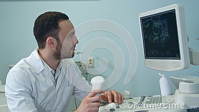 Concentrated male doctor looking at ultrasound scan results