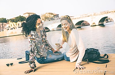 Happy multiracial girlfriends having fun with mobile smart phone