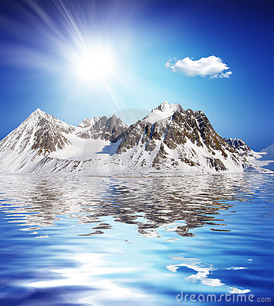 Snowcovered high mountain besides a lake with nice