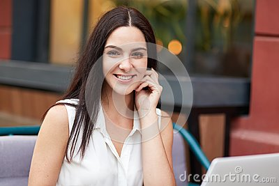 stock image of people, beauty, lifestyle and recreation concept. beautiful brunette female with pleasant smile, has appealing appearance, sits ag