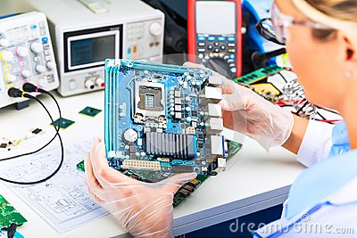 Female electronic engineer examining computer motherboard in lab