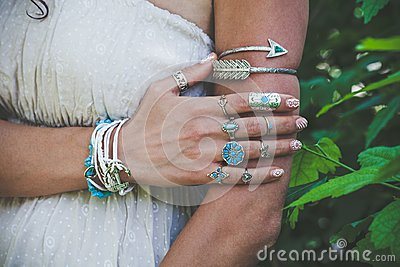closeup of young woman hand and arm with lot of boho style jewrly, rings and bracelets outdoor shot