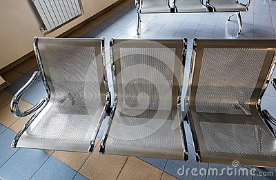 Three empty seats in waiting area of airport