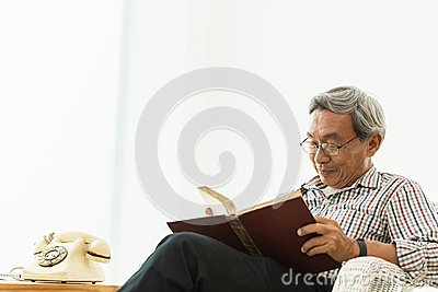 Asian Old man glasses professor sitting on the chair reading textbook
